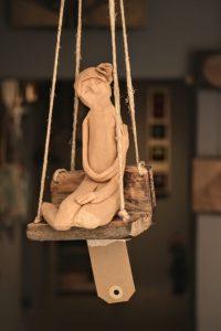 scultura in terracotta altalena